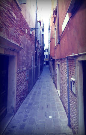street called CALLE in Italian Language  between tall houses in Venice Italy Banco de Imagens