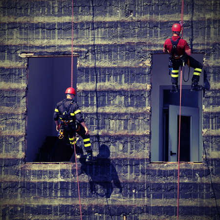 bold and daring climbers of firefighters climbing a wall of a house