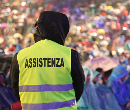 italian security guard during the important event with text ASSISTENZA that means Assitance in Italian language and many people while raining