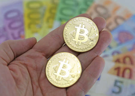 Hand with two big goden BITCOINS and blurred euro banknotes on the background Stock Photo