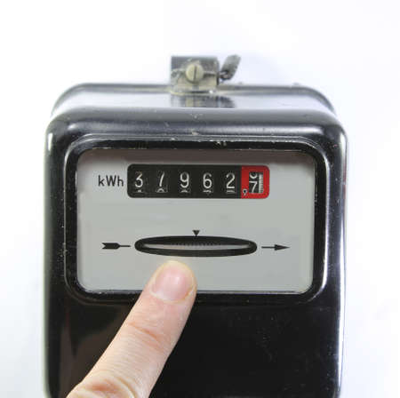 index finger indicating the consumption of electricity on a electricity meter on white background Stock Photo