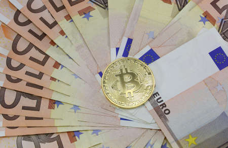 background of 50 euro banknotes and the golden BitCoin coin
