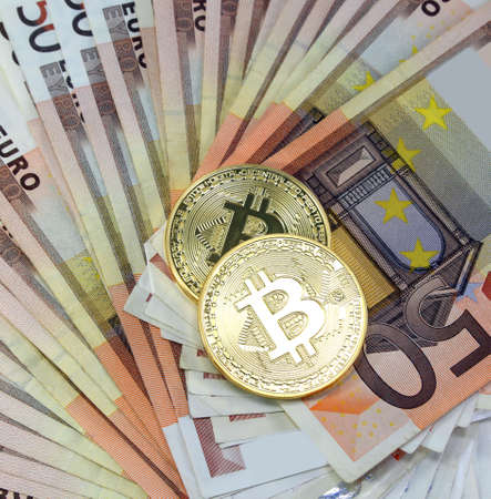 two big golden BitCoin coins over a lot of euro banknotes