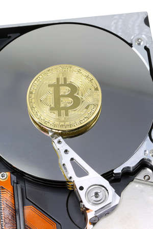 golden coin of BITCOIN on a computer hard drive Stock Photo