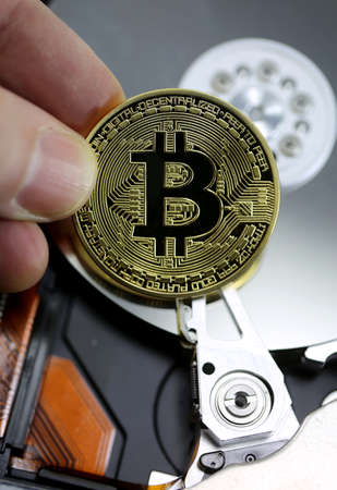 hand holds the big golden coin of BITCOIN symbol of the new crypto currencies and the background of a hard disk of a personal computer Stock Photo