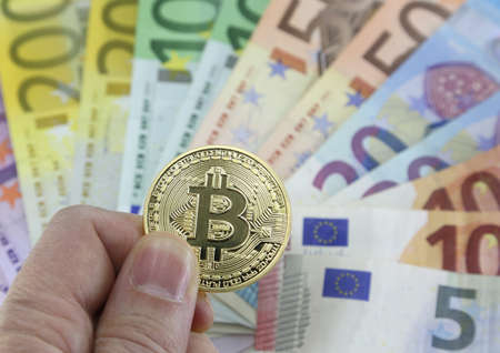 Hand with one big goden BITCOIN and blurred euro banknotes on the background