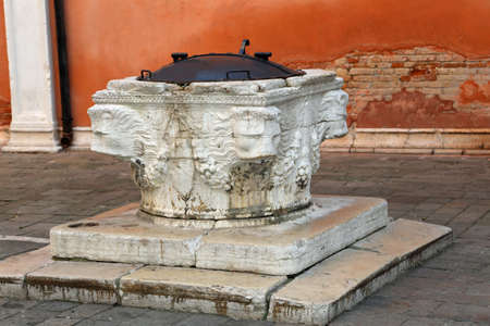 ancient well of marble in backyard   in Venice Italy Stock Photo