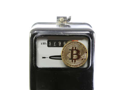 big golden BitCoin coin over an analog electric power meter Stock Photo