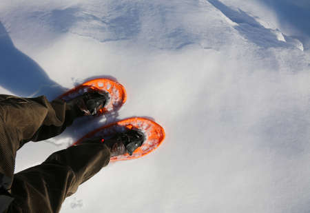 man walks with velvet pants or corduroy trousers in winter usinge two orange snowshoes