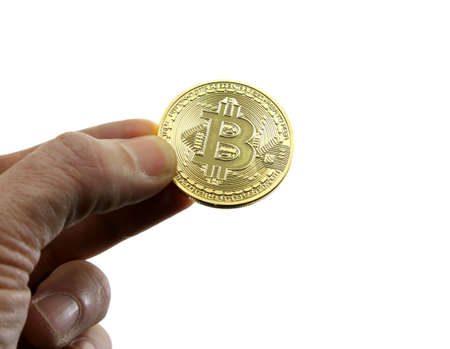hand holds the big golden coin of BITCOIN symbol of the new crypto currencies and the white background Stock Photo