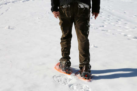 adult man walks with snowshoes in winter Stock Photo
