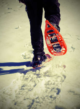 Man walks with snowshoes and corduroy pants on white fresh snow with vintage effect Stock Photo