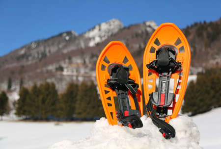 two orange snowshoes in mountains in winter with snow Stock Photo