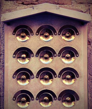 many golden doorbells in the european house with vintage effect