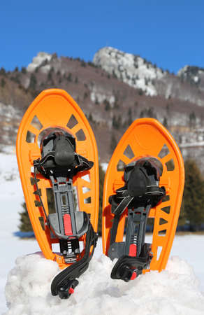 two orange snowshoes in winter in mountains Stock Photo