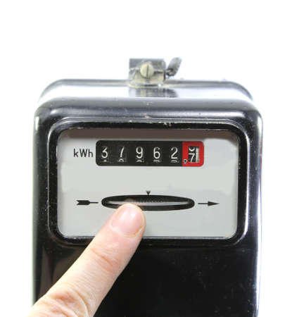 index finger indicating the consumption of electricity on an old electricity meter
