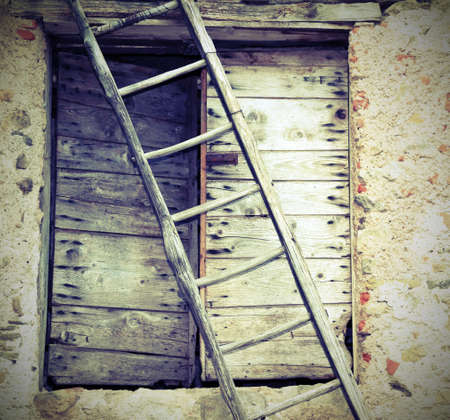 rural Scene with ancient ladder and a wooden old door of a farm with vintage effect Stock Photo