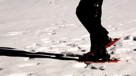 man snowshoeing uses orange snowshoes  in winter with dark special effect