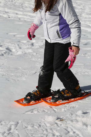 little girl with sportwear and orange snowshoes in winter