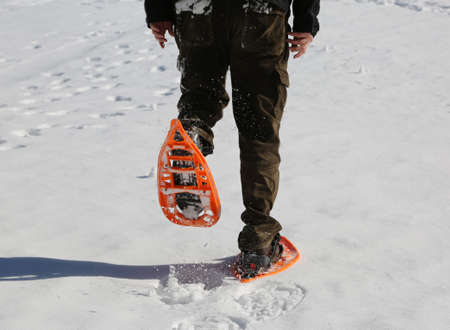 Man walks with modern orange snowshoes and corduroy pants on white fresh snow in mountains Stock Photo