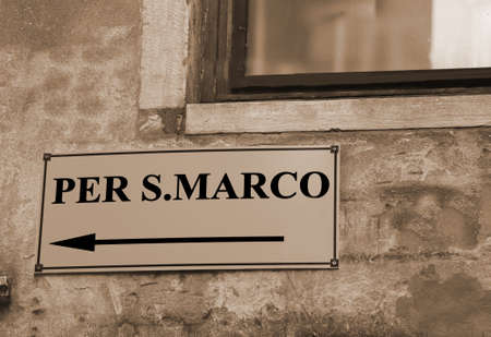 signpost with directions to go to St. Marks Square in Venice in Italy with sepia toned Stock Photo