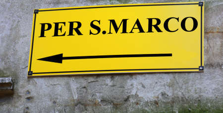 yellow Street sign with directions to go to St. Marks Square in Venice Stock Photo