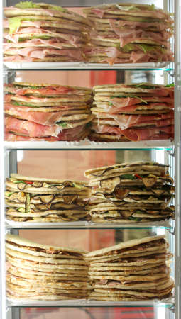 Refrigerator with lots of stuffed sandwiches called Spianata or Piadina in Italian language for sale