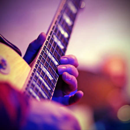 Guitarist plays electric guitar on stage during a live concert with vintage effect