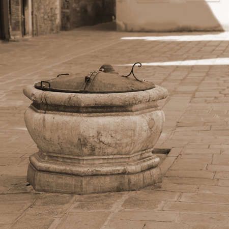 very ancient stone well in a square of VENICE in Italy with sepia toned Stock Photo