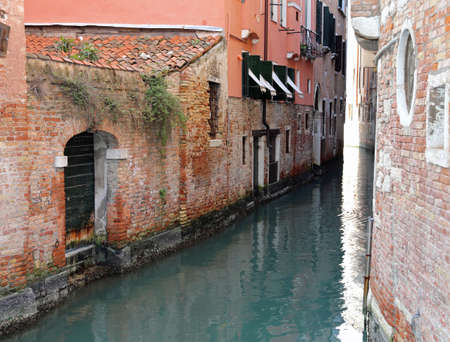 Venice Italy A Narrow Canal with old houses with low tide Stock Photo - 96287882