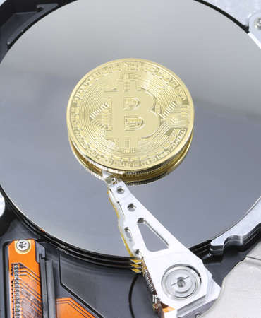 computer hard drive and a large golden BITCOIN coin symbol of the new crypto currencies Stock Photo