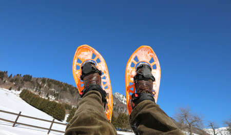 two legs with corduroy pants and orange snowshoes in winter and blue sky on background