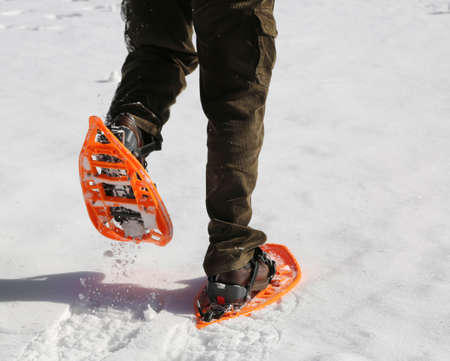 Man with corduroy trousers with snowshoes on white snow Stock Photo