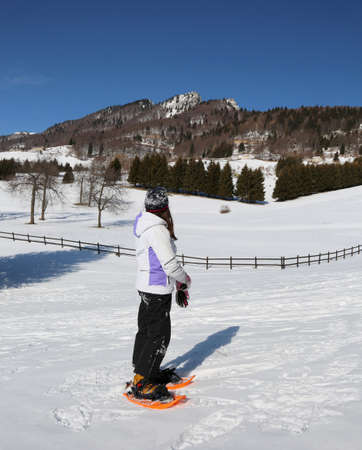 mountains panorama and a little girl wirh sportwear and orange snowshoes in winter Stock Photo