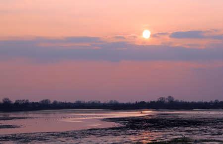 sun at sunset on venetian lagoon at winter