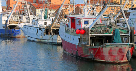 red fishing boat in the waterway with many others boats 写真素材