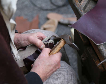 hand of the cobbler repairs the shoe with an ancient hammer and the piece of leather