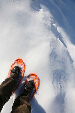 man with orange snowshoes walks near a deep crevasse Stock Photo