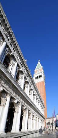 Saint Mark square and ancient Palace of  National Library called Biblioteca Marciana with high tide and tall bell tower in Venice Italy Stock Photo