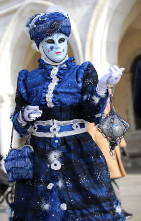 Venice, Italy - February 5, 2018: woman in blue costume with carnival mask Editorial