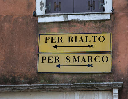 Venice Italy road sign with indication to Railto Bridge or Saint Mark Square with two black arrows Stock Photo