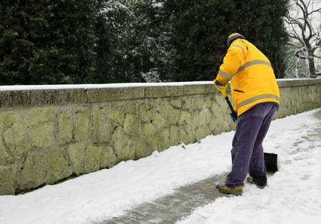 garbage man shovels the snow from the sidewalk after snowfall Stock Photo