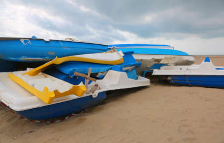 pedalos destroyed in a beach carried by the current after a storm