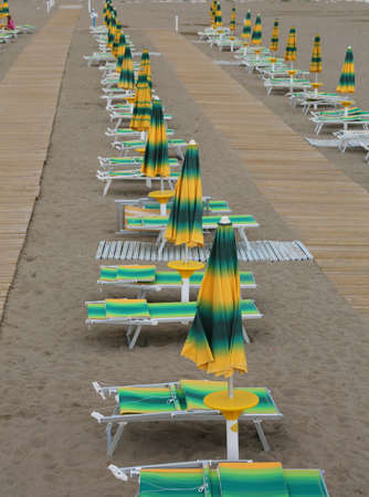 yellow and green beach chairs and umbrellas arranged along an Italian beach