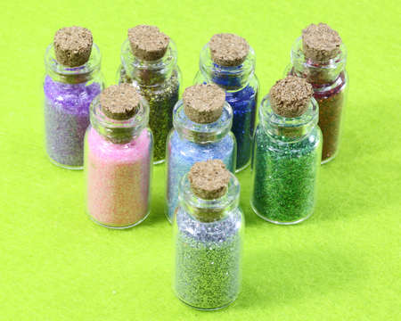 glass flasks with glitter and a green background Stock Photo