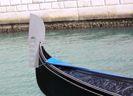 metallic bow of the gondola in a waterway in Venice Italy