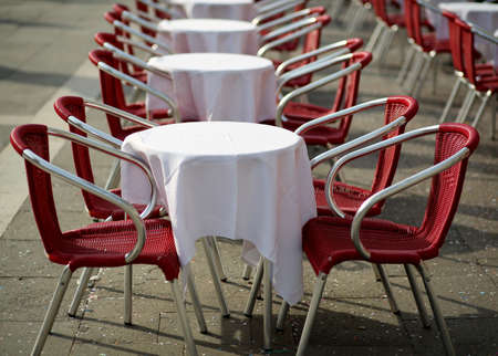 tables and red chairs in an alfresco cafe in europe