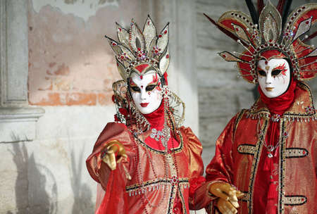 Venice, Italy - February 5, 2018: woman and man with fantastic red and golden dress under the ducal Palace