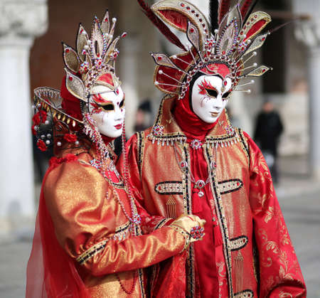 Venice, Italy - February 5, 2018: woman and man with fantastic red and golden dress near the Ducal Palace during the Venetian Carnival Editorial