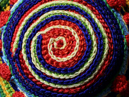 colored pinwheel with woven threads in the shape of a circle
